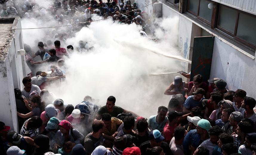 رجال الشرطة يرشون مئات المهاجرين بطفايات الحريق في محاولة لتفريقهم