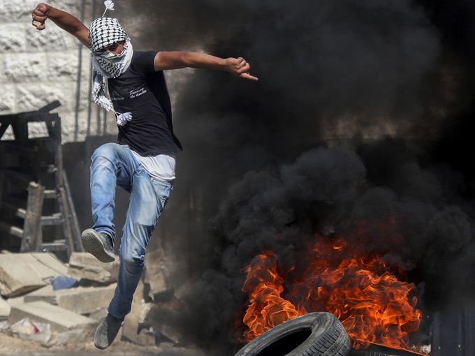 صور حول العالم متظاهر فلسطيني يلقي الحجارة على قوات الاحتلال الصهيوني