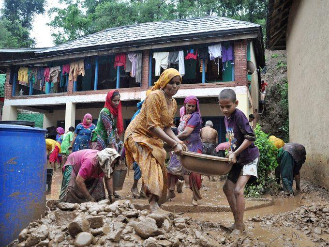 عائلة هندية تنظف ساحة منزلها من الطين بعد تضرر المباني من انهيارات طينية بسبب الأمطار الغزيرة في ولاية جالوت.