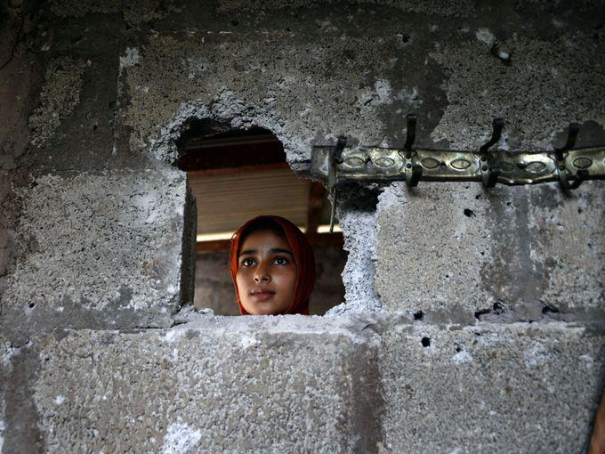 فتاة تتفقد جدار منزلها الذي تعرض للضرر بسبب إطلاق قذيفة هاون على منزلها في كشمير الباكستانية.