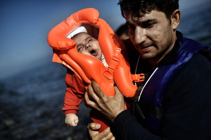 مهاجر يحمل طفلا